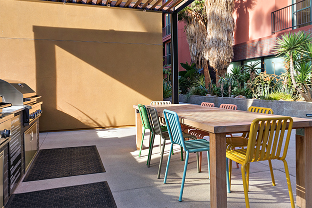 Outdoor grilling area with pergola, wood dining table with colorful metal chairs, and built in BBQ grills.