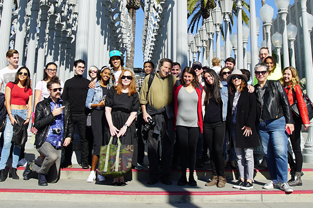 Large group of people standing in front of Urban Lights art installation at LACMA.