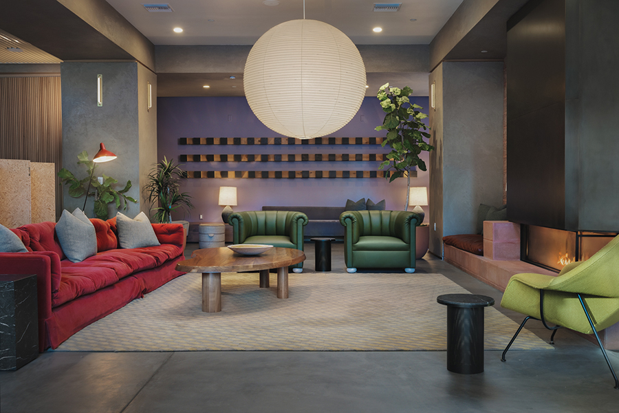 Lounge with pattern rug, comfortable plush couches, fireplace, and hanging paper lantern.