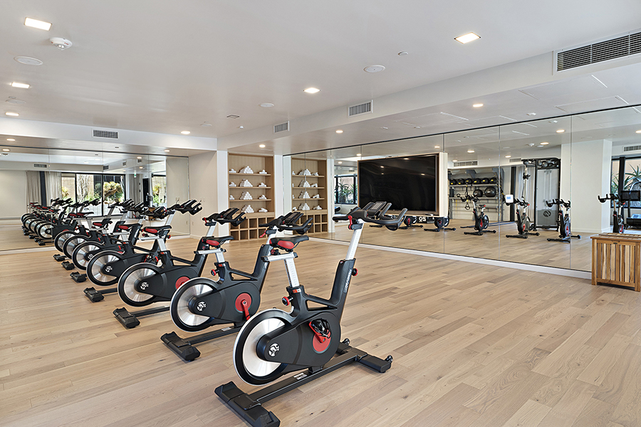 Spin room with light wood floors, rows of spin bikes, and mirror wall.