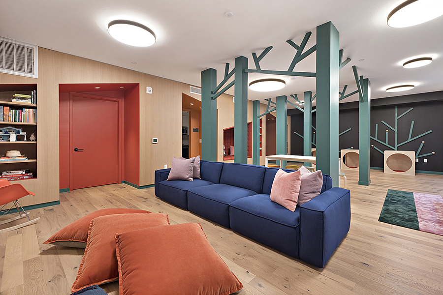 Kids play area with soft colorful couches, decorative tree columns, small kids table, and bookshelves.