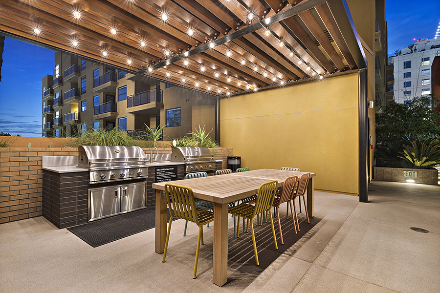 BBQ area with pergola with string lights, built-in BBQ grill, and large dining table.