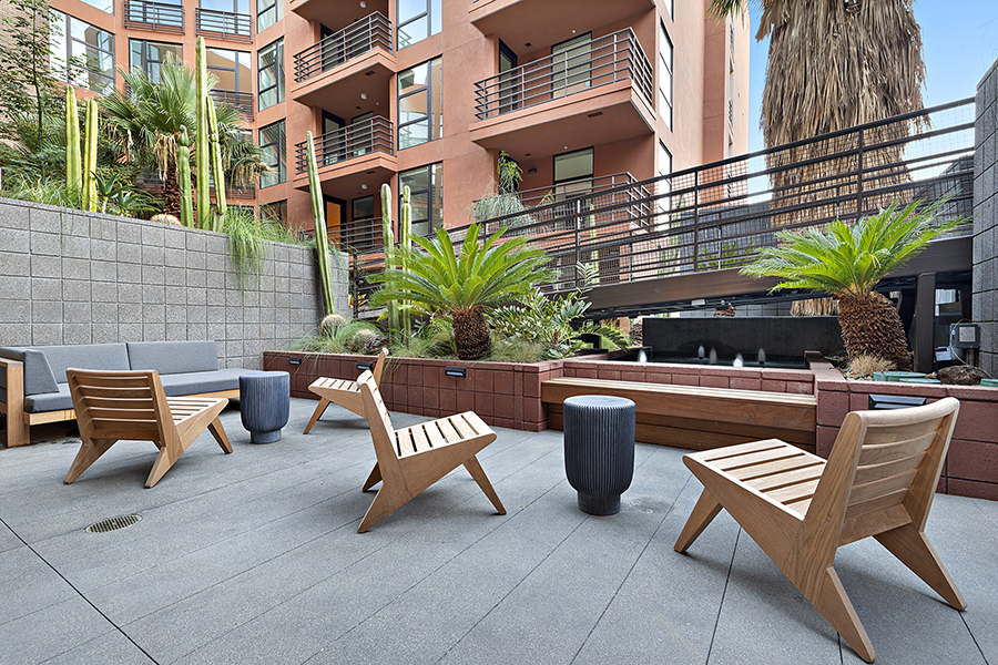 Outdoor lounge with plush couch, modern wood lounge chairs, and fountains under tall palm trees.
