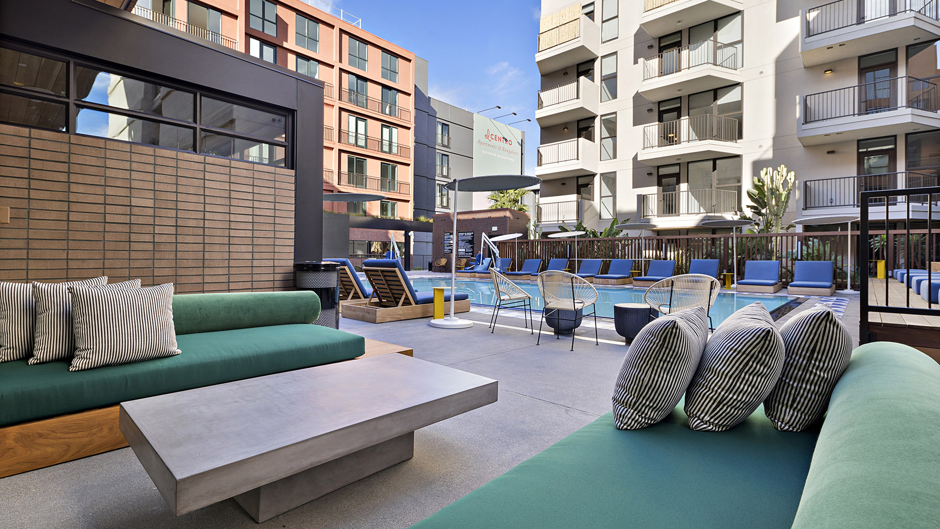 Outdoor lounge with comfortable plush couches and stone table with pool area and apartments behind.