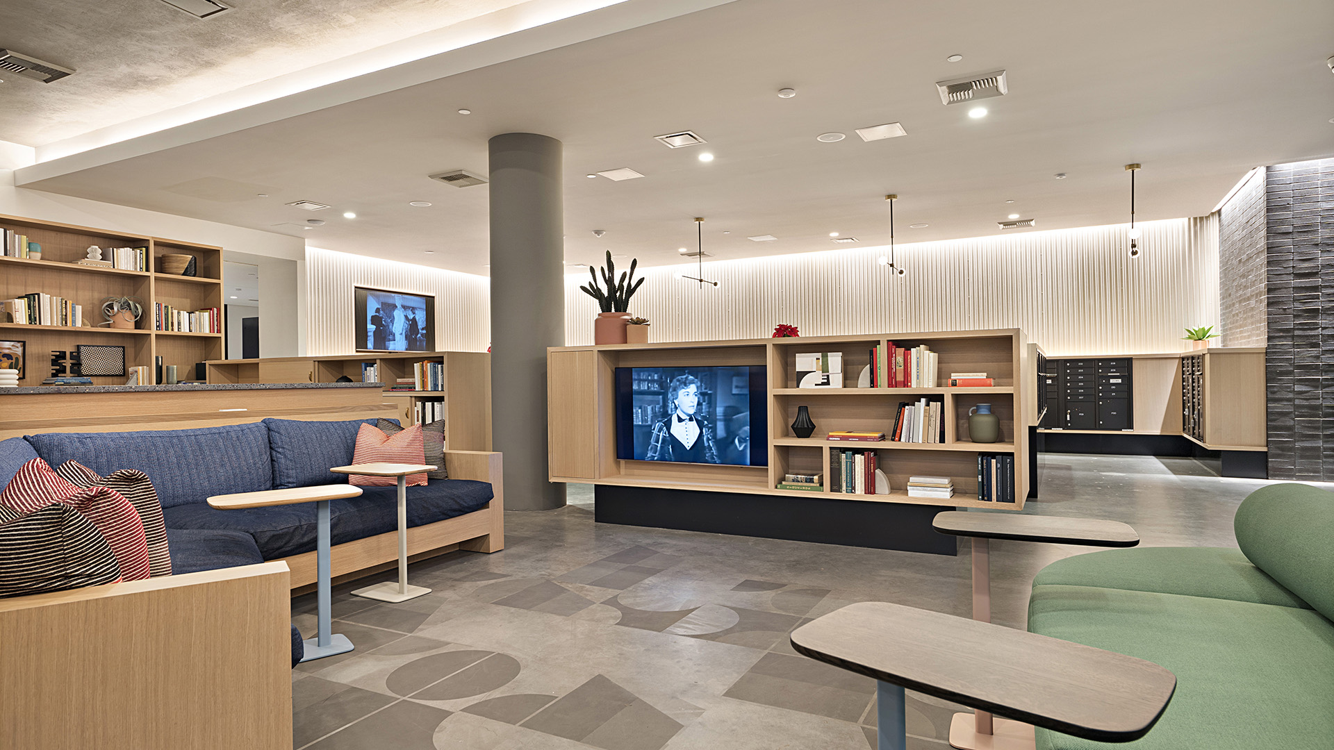 Lobby area with modern built-in seating, credenza with TV and bookshelves, and geometric floor pattern.