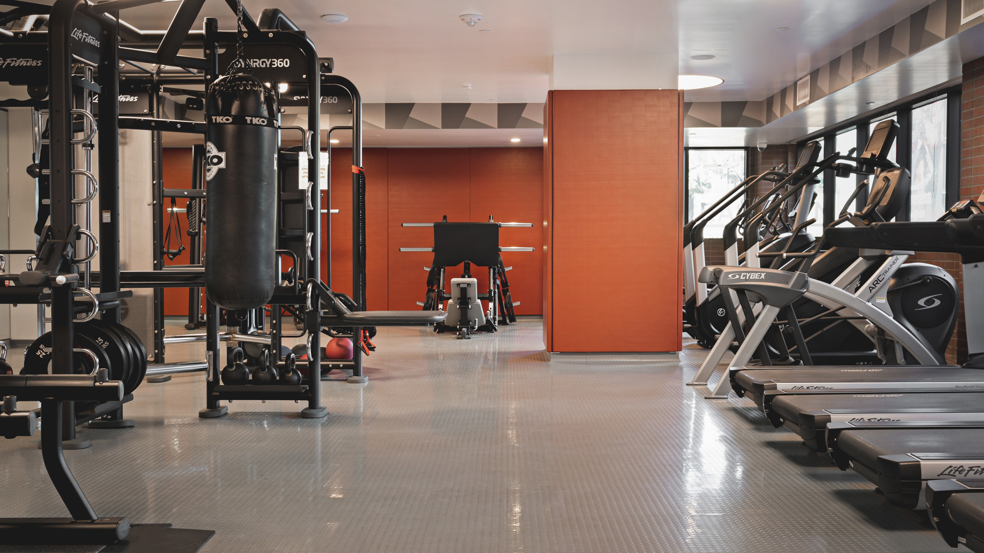 Fitness center with gym flooring, rows of cardio equipment, weight machines, and free weight racks.