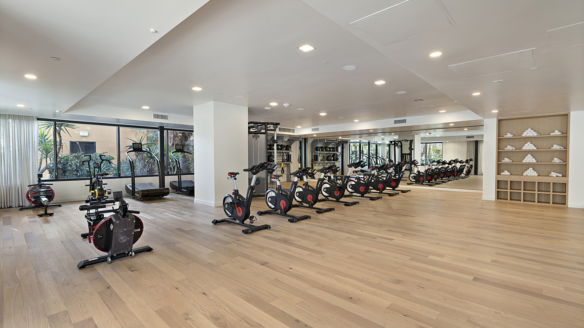 Yoga and spin room with light wood floors, mirror wall, rows of spin bikes, and open space for yoga.