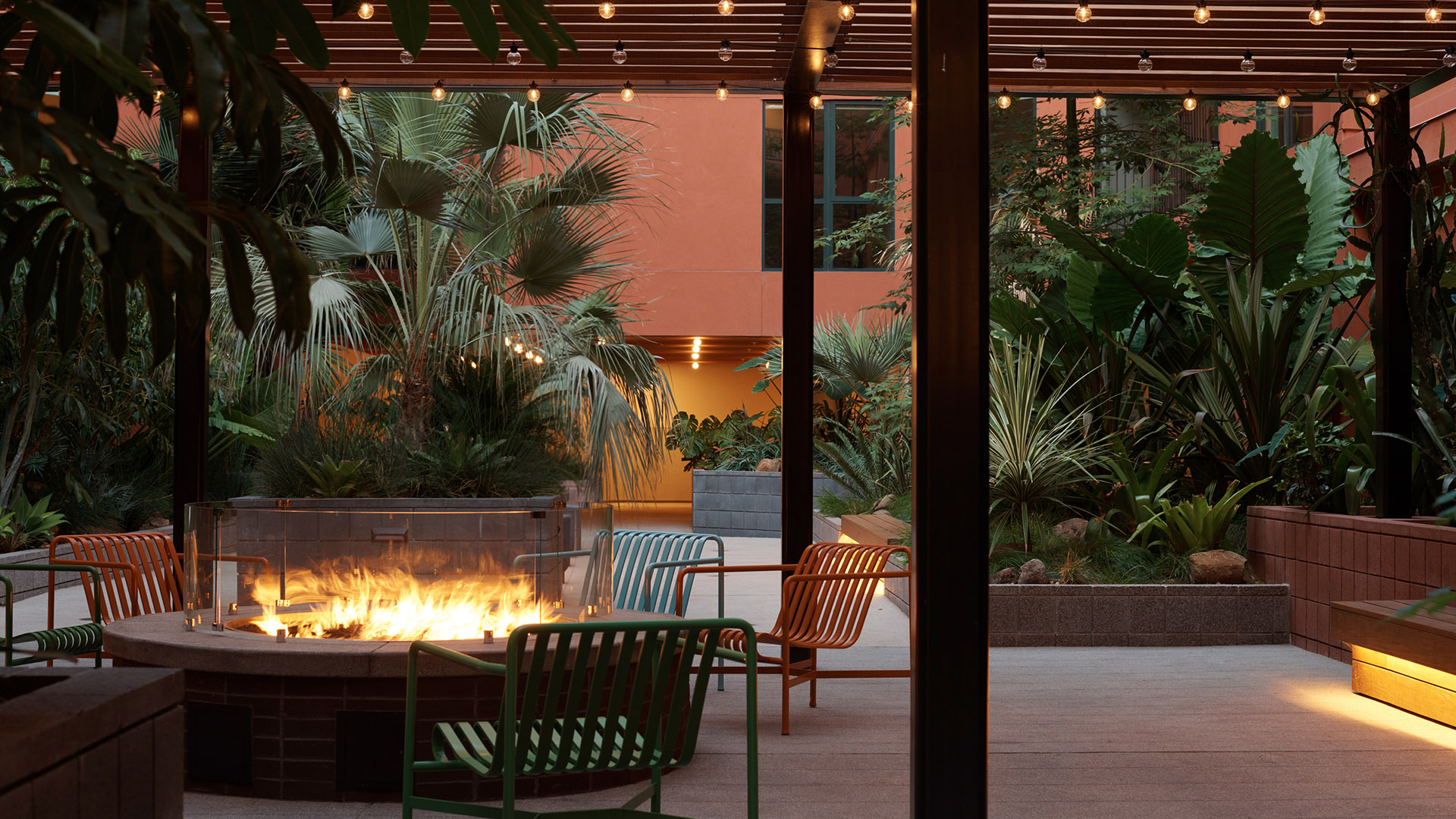 Outdoor lounge area with glowing firepit, colorful metal lounge chairs, and built in planters with tropical plants.