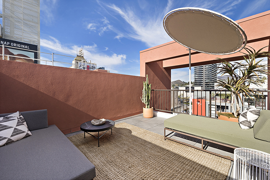 Rooftop balcony with pavers, outdoor rug, plush outdoor couches, and round sun shade.
