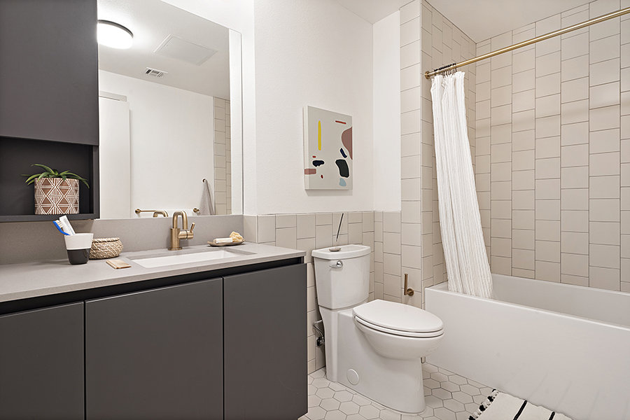Bathroom with hexagonal tile floors, grey cabinets with single vanity, and tiled shower/tub with curtain.