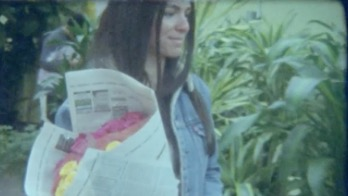 Flavia holding bouquet wrapped in newspaper.