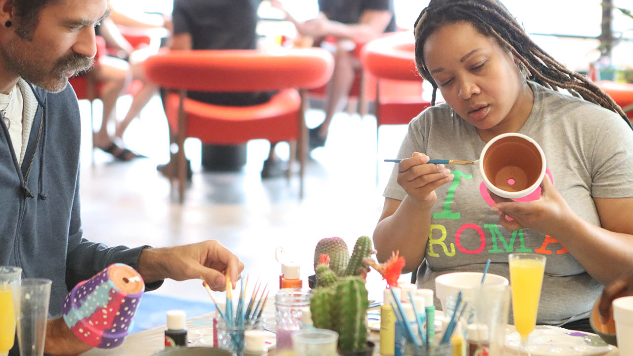 Two residents sitting at table and painting small plant pots at the CactusCraft event.
