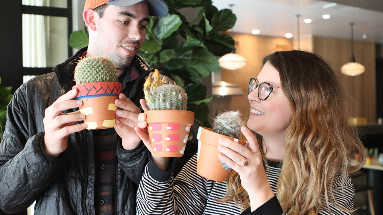 Two residents smiling at each other holding their cactus plants from the CactusCraft event.