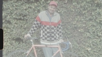 Will wearing checkered jacket and holding bicycle.